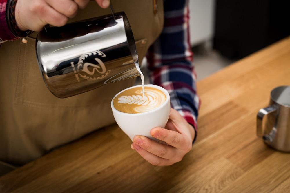 mobilny barista rysujący na kawie rozetę wzór latte art
